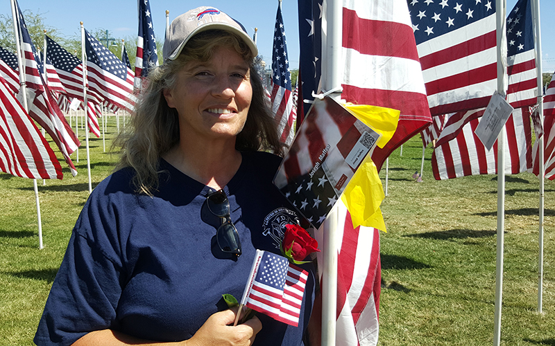 Phoenix mail carrier Angela DiMaria places roses on the flagpoles of firefighters who died during the 9/11 terrorism attacks. She visits the Healing Field in Tempe every year. (Photo by Michelle Chance/Cronkite News)